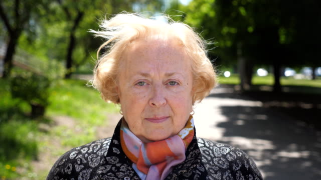 Portrait of beautiful elderly woman seriously and pensive looking at camera. Senior caucasian lady of retirement age is standing in urban city background. Sight of grandmother outdoor. Close up