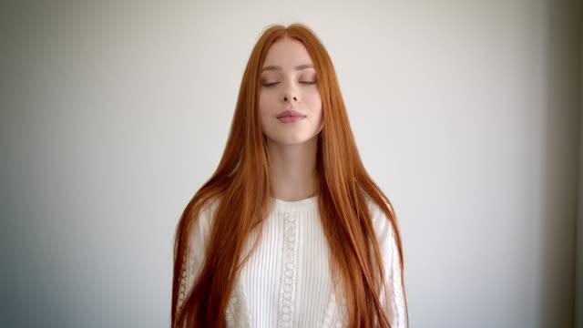 porträtt av vacker ingefära elev tittar lugnt i kameran på vit bakgrund. - rött hår bildbanksvideor och videomaterial från bakom kulisserna