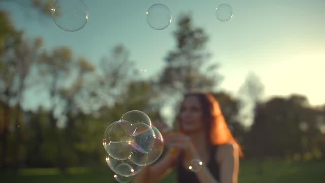 生姜の美しい若い女性の肖像画。公園でシャボン玉を吹く - 春のファッション点の映像素材/bロール