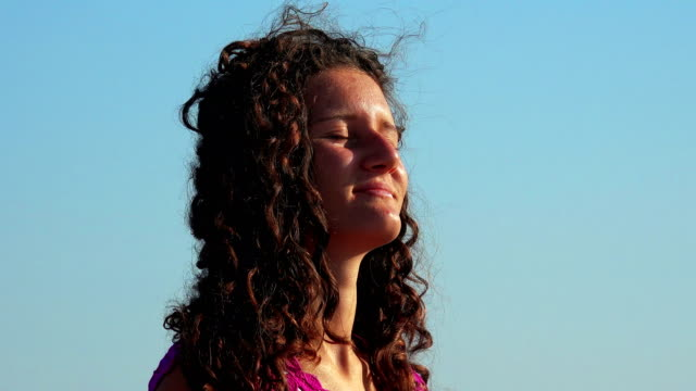 Portrait of beautiful girel enjoying summer wind at sunset