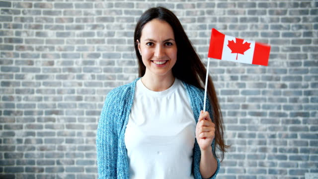 portrait of beautiful girl holding canadian flag on brick wall background - canada flag stock videos & royalty-free footage