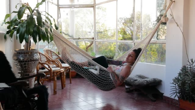 portrait of beautiful latina /mexican millennial woman with tattoos relaxing in hammock at home - amaca video stock e b–roll