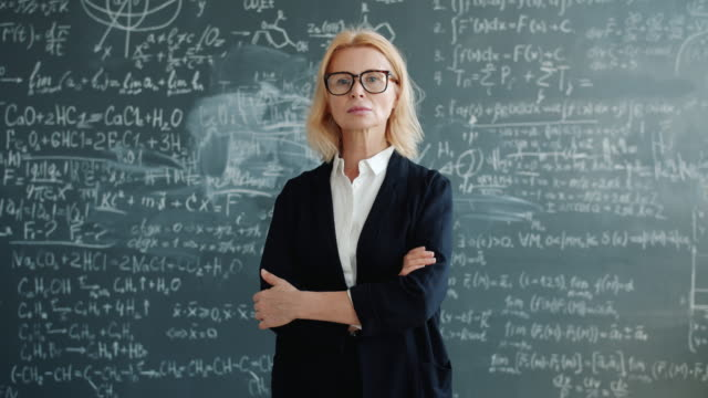 portrait of beautiful mature woman in suit standing near chalkboard with arms crossed - formula 1 стоковые видео и кадры b-roll