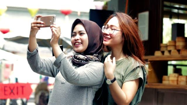 笑顔カメラとトーンの 3 種類の撮影 selfies のイスラム教徒やアジアの美しい女性の肖像画 (シアン - オレンジ色、コントラスト、および raw) - インドネシア点の映像素材/bロール