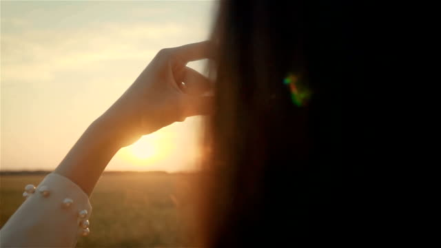 Portrait of beautiful pretty young woman holding heart shaped hands near face at sunset in yellow field