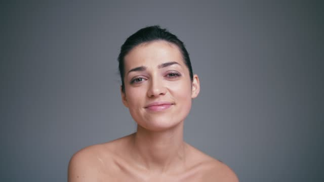 Portrait of beautiful smiling happy brunette woman with bright eyes. Slow motion skincare concept
