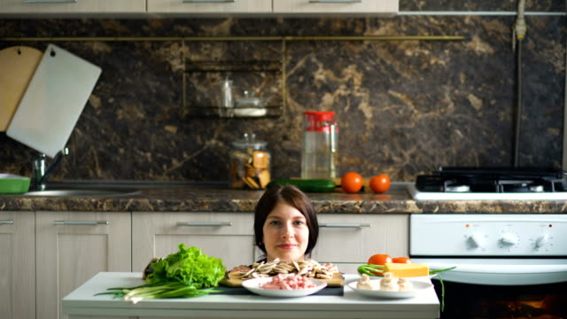 Portrait of beautiful smiling woman cook show above the table with vegetables in kitchen at home video