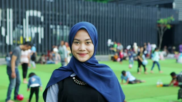porträtt av vackra söder östasiatiska muslimsk kvinna med hijab leende på kamera med två slags toner - hijab bildbanksvideor och videomaterial från bakom kulisserna