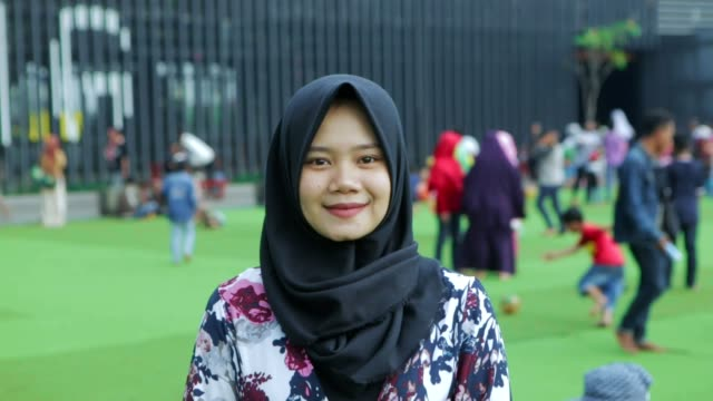portrait of beautiful south east asian muslim woman with hijab smiling on camera with two kind of tones - hijab video stock e b–roll