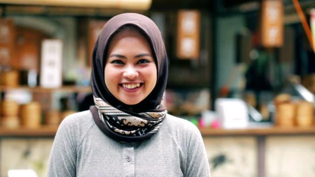 porträtt av vackra söder östasiatiska muslimsk kvinna med hijab leende på kamera med tre slags toner (cyan - orange, kontrast, och rå) - hijab bildbanksvideor och videomaterial från bakom kulisserna