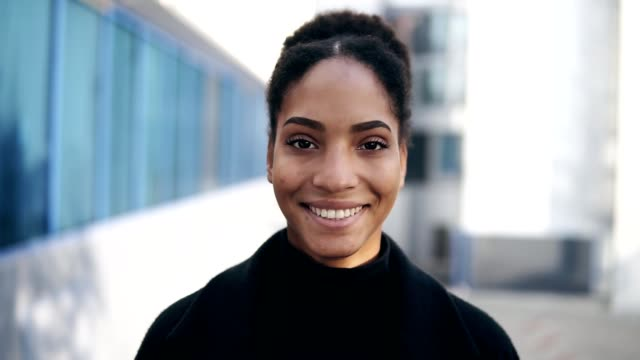 Portrait of beautiful stylish african american woman smiling at camera looking confident. Wearing black clothes, urban city background. Real people series