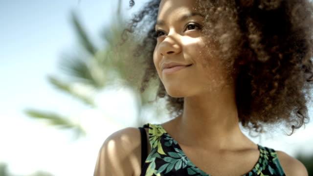 stockvideo's en b-roll-footage met portret van mooie afro amerikaanse tienermeisje op tropisch strand lacht om een camera. - afro amerikaanse etniciteit
