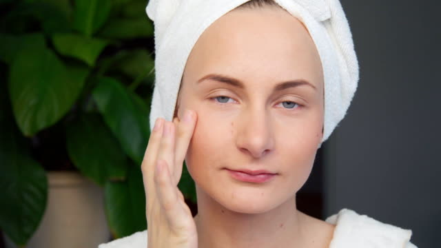 Portrait of beautiful woman applying cream on her face video