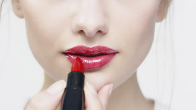 Portrait of beautiful woman applying red lipstick Close-up of woman applying red lipstick. Portrait of beautiful woman with blue eyes. She is staring against white background. red lipstick stock videos & royalty-free footage