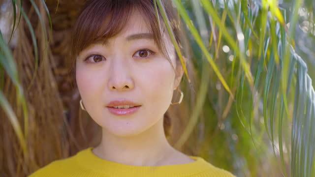 stockvideo's en b-roll-footage met portret van mooie vrouw in gele trui in aard - aziatische etniciteit