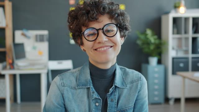 stockvideo's en b-roll-footage met portret van mooie vrouw die op glazen zet en glimlacht die camera in bureau bekijkt - bril brillen en lenzen