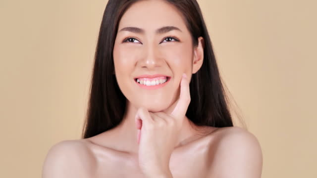 Portrait of beautiful woman smiling on brown background.Beautiful woman touching her face.Expressive facial expressions.Cosmetology and Spa