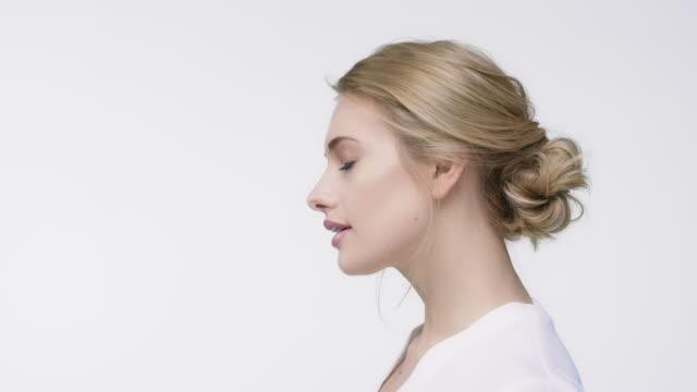 vidéos et rushes de portrait de la belle femme aux cheveux blonds - vue latérale
