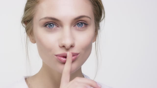 dudaklarında parmak ile güzel bir kadın portresi - cilt bakımı stok videoları ve detay görüntü çekimi