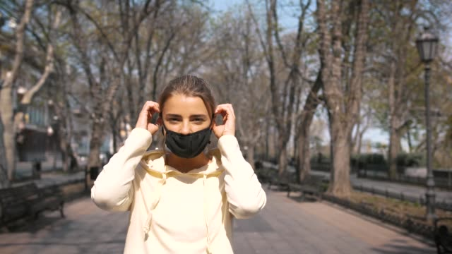 portrait of beautiful young and fit woman putting on protective face mask in city center park - nakładać filmów i materiałów b-roll