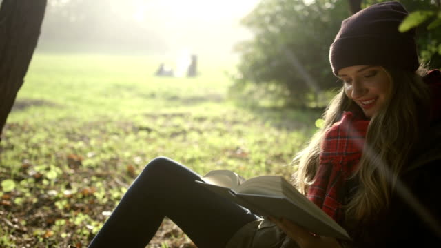 Portrait of beautiful young caucasian girl reading a book in the autumn park. video
