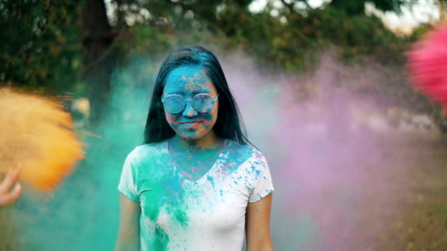 vídeos de stock e filmes b-roll de portrait of beautiful young lady in sunglasses enjoying holi festival standing outdoors while people are throwing colorful powder in her. culture and traditions concept. - holi