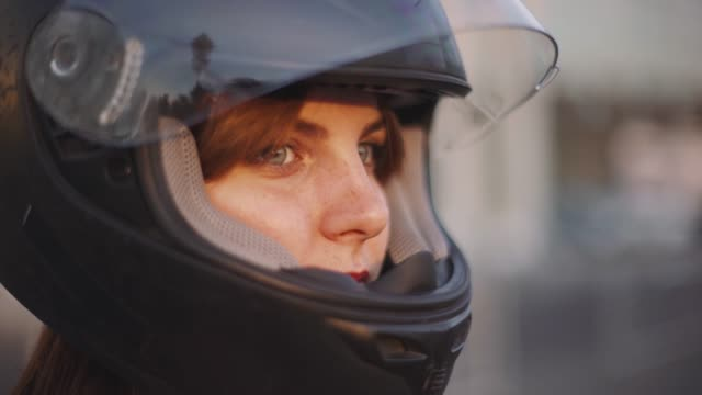 portrait of beautiful young red-haired woman motorcyclist in helmet at sunset