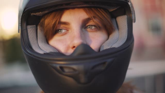 portrait of beautiful young red-haired woman motorcyclist in helmet at sunset portrait of beautiful young red-haired woman motorcyclist in helmet at sunset  in Odessa crash helmet stock videos & royalty-free footage