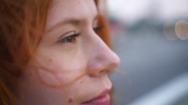 портрет красивая молодая рыжая женщина изучает духовность созерцая будущее с ветер дует волосы - mindfulness стоковые видео и кадры b-roll