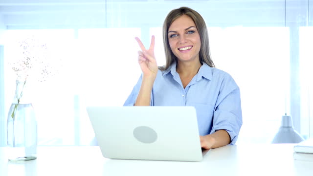 portrait of beautiful young woman gesturing  victory sign - campionato video stock e b–roll