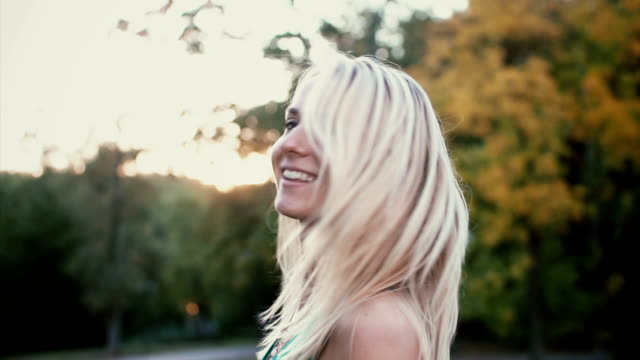 Portrait of beautiful young woman in park on sunset. Blonde girl turns and looks at camera, her hair waves. Slow motion Portrait of beautiful young woman in park on sunset. Blonde girl turns and looks at camera, her hair is waves in wind. Happy girl spending evening outside. Slow motion. expressionism stock videos & royalty-free footage