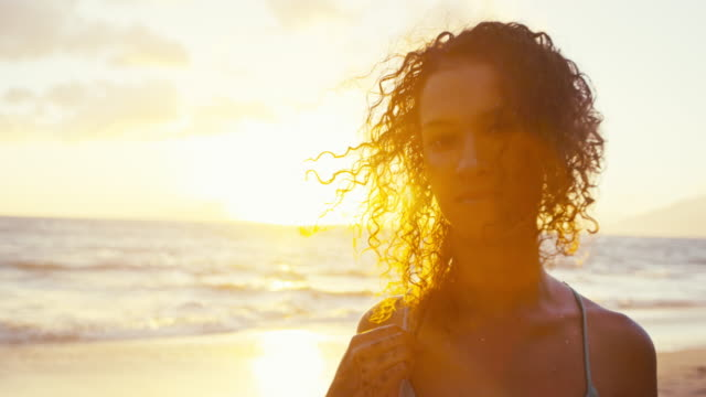 Portrait of beautiful young woman on the beach at sunset video
