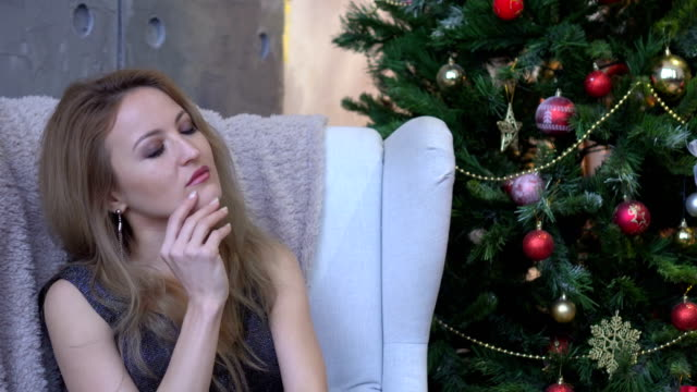 Portrait of beautiful young woman thinking and looking upwards near christmas tree. video