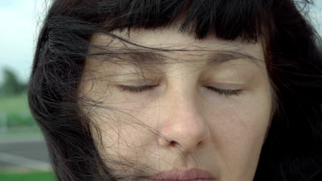 Portrait of beautiful young woman with closed eyes closeup. Wind blowing hair. Slow Motion. Attractive woman  brunette confident pretty. Windy weather. Portrait of beautiful young woman with closed eyes closeup. Wind blowing hair. Slow Motion. Attractive woman  brunette confident pretty. Windy weather. eyes closed videos stock videos & royalty-free footage