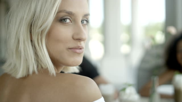 Portrait of beautiful young woman with friends at outdoor cafe. video
