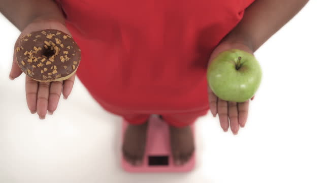 portrait of black woman with overweight on the scales who choosing between donut and apple and in the end prefers donut isolated on white background