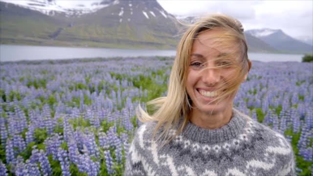 portrait of blond hair woman in lupine flower field in iceland near lake and mountains. people travel happiness concept -slow motion - spettinato video stock e b–roll