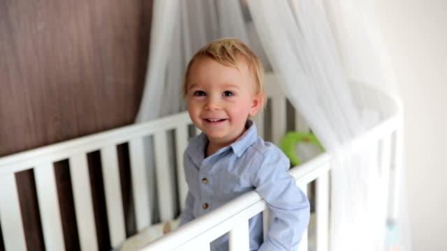 porträtt av uttråkad baby stående i spjälsängen. baby pojke stå ensam i spjälsängen. ledsen liten bebis. - byxor bildbanksvideor och videomaterial från bakom kulisserna