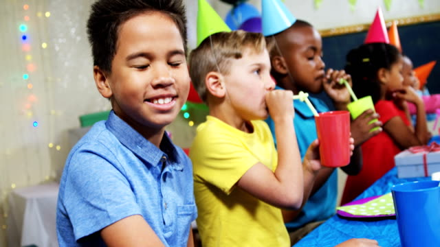 Portrait of boy sitting with friends during birthday party 4k video