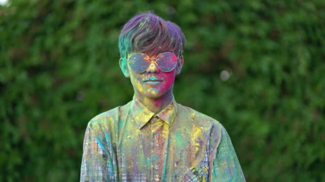 ホーリーフェスティバルで色付きの粉末で覆われている少年の肖像画。 ビデオ