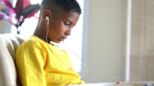 タブレット上で再生中の音楽をブラジルの子供の肖像画 - ゲーム ヘッドフォン点の映像素材/bロール