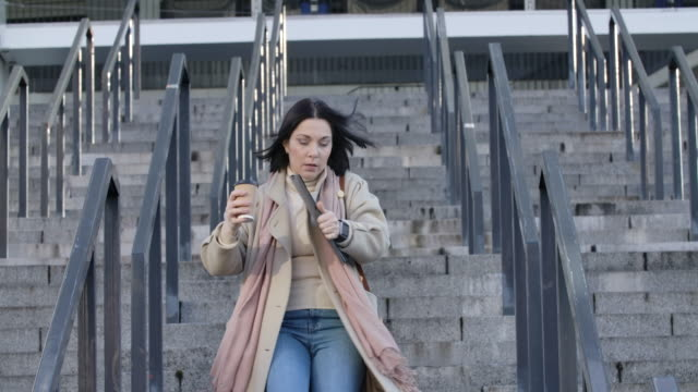 vídeos de stock e filmes b-roll de portrait of brunette adult woman running down the stairs with coffee cup and folder with documents and looking at her watch. young caucasian businesswoman late for meeting. cinema 4k prores hq. - important