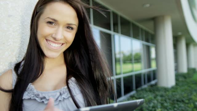 porträtt av brunett kaukasiska kvinnlig student med pekskärm - stavning bildbanksvideor och videomaterial från bakom kulisserna