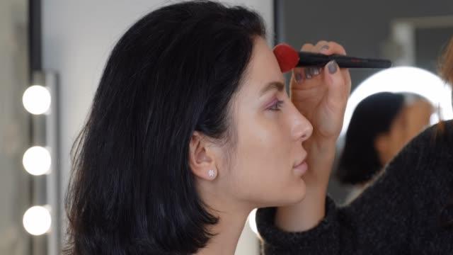 porträtt av brunett flicka make-up artist i ansiktet tillämpa pulver med professionell borste i makeup studio på bakgrund av bokeh glödlampor på spegel slow motion. smink och skönhet - makeup artist bildbanksvideor och videomaterial från bakom kulisserna