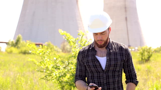 Portrait of Builder in helmet and phone outdoors. video