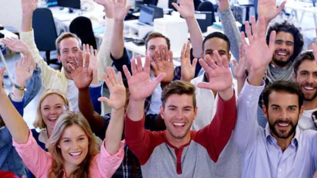 Portrait of business team gesturing together in office video