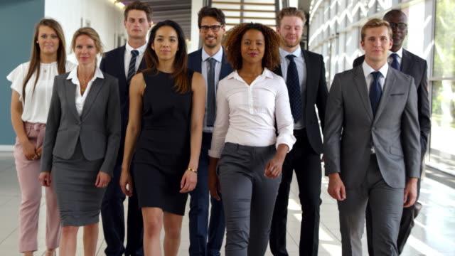 porträt des business teams zu fuß in richtung kamera im büro - team stock-videos und b-roll-filmmaterial