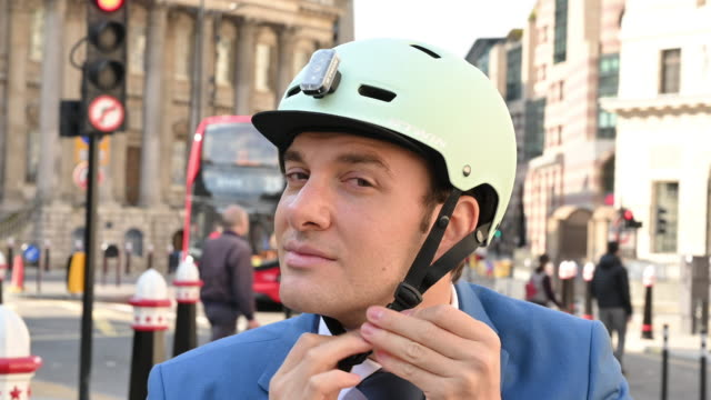 Portrait of businessman putting on and removing bike helmet