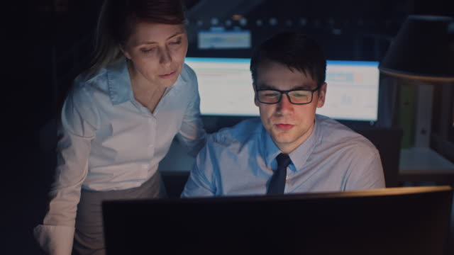 Portrait of Businessman Uses Desktop Computer, His Female Project Manager Explains Specific Tasks, Account Handling and Strategic Moves. Professional People Late at Night in Big Corporate Office