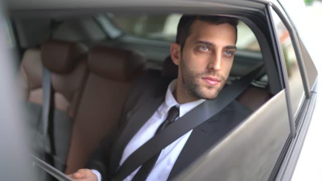 vídeos de stock, filmes e b-roll de retrato do homem de negócios que usa a tabuleta digital dentro do carro - dividindo carro